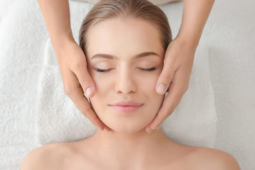 Young woman enjoying of facial massage in spa salon