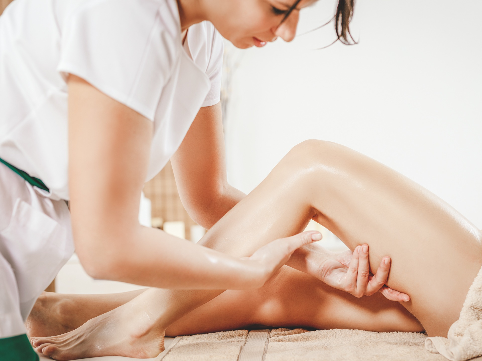 Young female massage therapist giving a relax massage to a client.