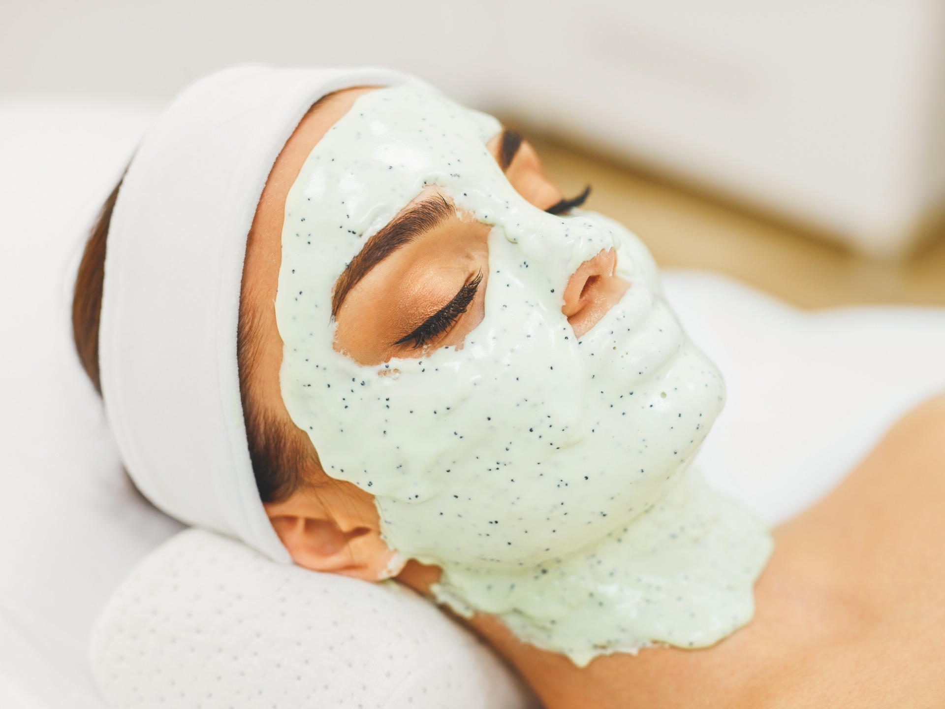 Woman Skin Care. Closeup Of Beautiful Girl With Cosmetic Mask On Facial Skin In Beauty Salon. Young Female With Face Covered With Green Moisturizing Alginate Mask. Beauty Treatment. High Resolution