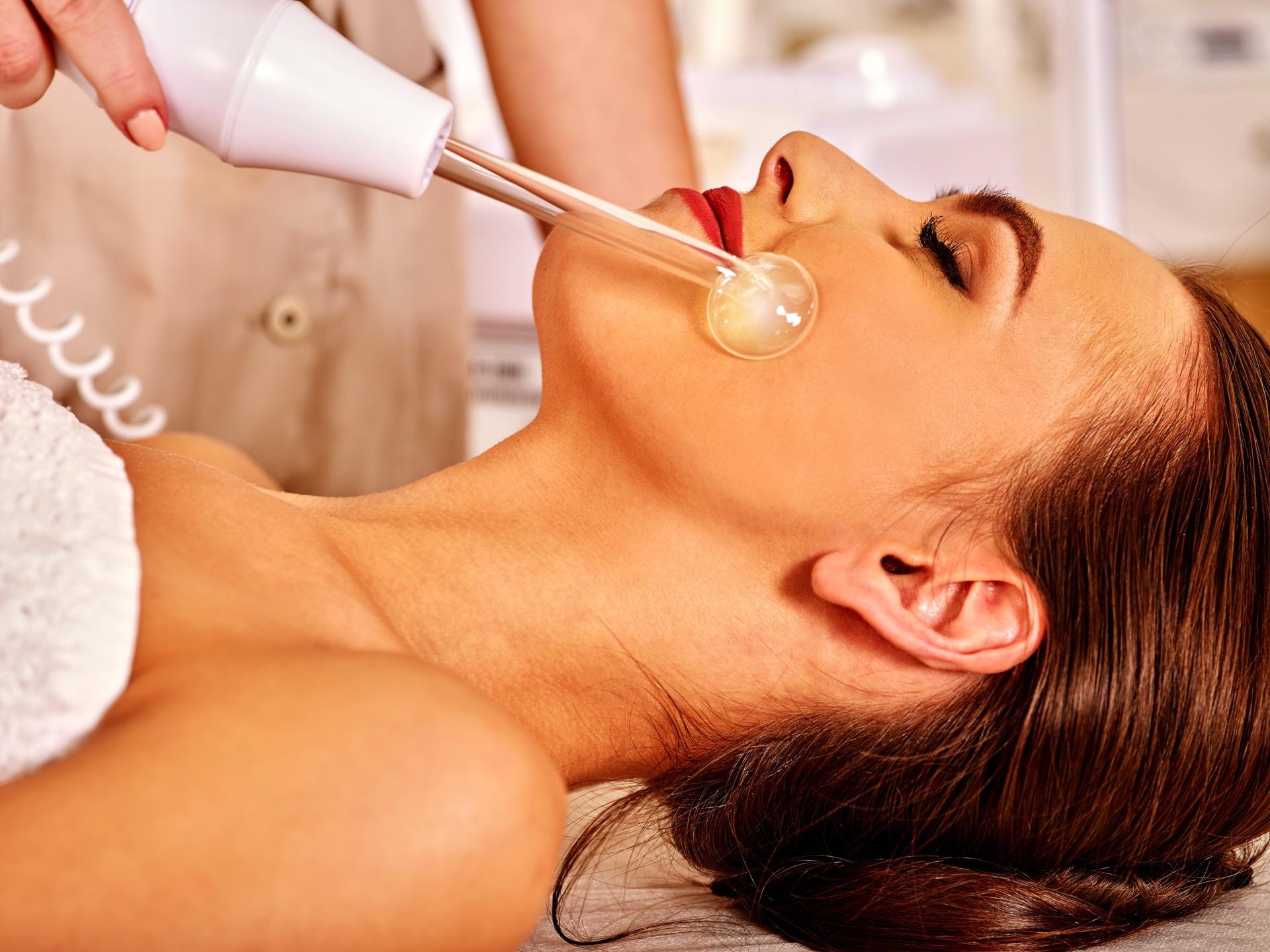Young woman receiving electric darsonval facial massage procudure after procedure .